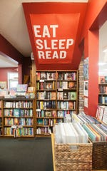 """A banner urging patrons to """"eat, sleep, read"""" hangs from the underside of the stairs to the second floor at Carmichael's Bookstore on Frankfort Avenue."""