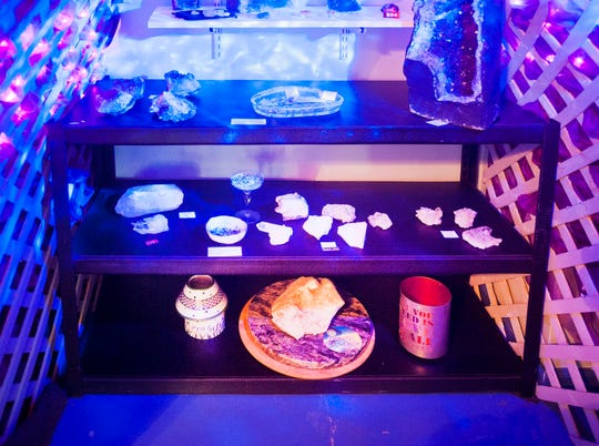 Quartz geodes light up in a black-lit room at the Louisville Rock Shop in Crescent Hill
