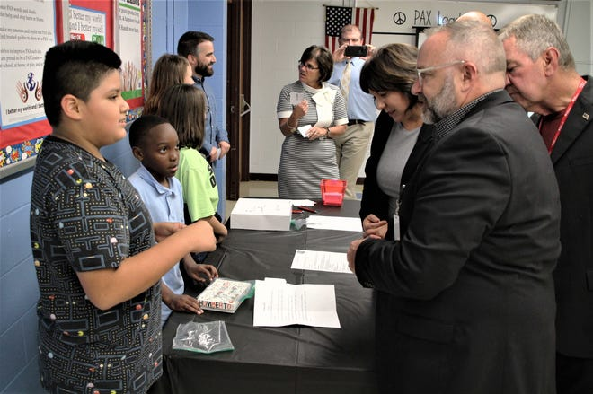George Washington Elementary School fifth grade student Humberto Garcia-Jiminez, left, explains a math game to members of the Marion City Schools board of education during the state of the schools meeting on Monday evening. The students taught the board members how to play the educational games.
