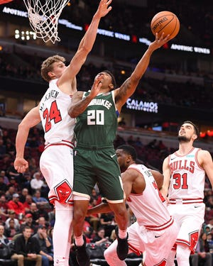 Bucks guard Jaylen Adams cuts through a trio of Bulls defenders for a layup Monday night.