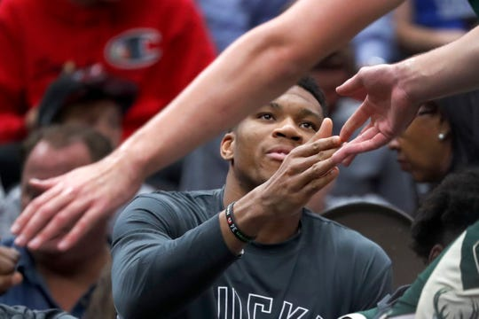 Milwaukee Bucks' Giannis Antetokounmpo welcome Dragan Bender back to the bench the bench during the second half of an NBA preseason basketball game against the Chicago Bulls Monday, Oct. 7, 2019, in Chicago. Antetokounmpo did not play in the team's 122-112 win