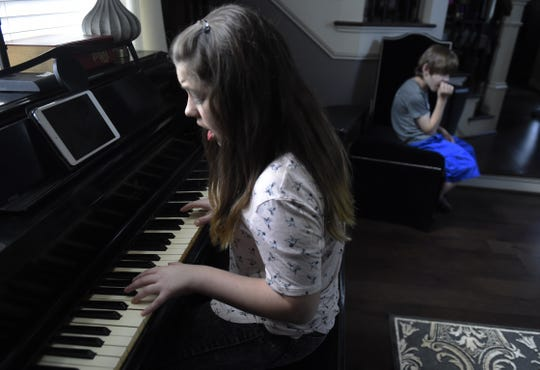 Lilah Petersson plays a song for her brother Liam at their home Wednesday April 20, 2016, in Brentwood, Tenn. The Petersson Family founded Rock Your Speech, which incorporates speech therapy into music, after Liam was diagnosed with Autism Spectrum Disorder.