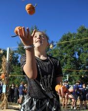 Olivia Roark tries to juggle pumpkins at the Cooper Trooper Pumpkin Patch in Cool Springs, Tenn. on Saturday, October 5, 2019.