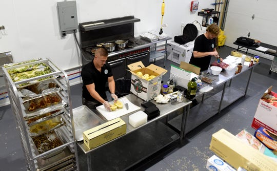 Josh Link, owner and CEO of Visionary Meals in Newark, prepares squash for roasting as chef Justin Gottschalk makes a spiced tomato ragout during a meal prep day for the local meal prep business. Customers order meals for pick up or delivery based on their dietary needs.