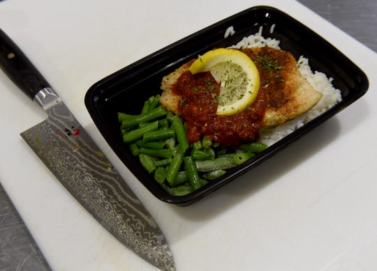 One of Visionary Meals' chef specialties Blackened Tilapia with Spiced Tomato Puree served on a bed of rice and with green beans.