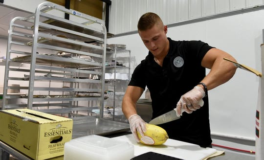 Josh Link, owner and CEO of Visionary Meals in Newark, prepares squash for roasting during a meal prep day for the local meal prep business. Customers order meals for pick up or delivery based on their dietary needs.