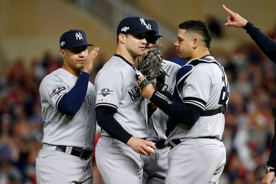 New York Yankees relief pitcher Tommy Kahnle, center, talks with teammates Gio Urshela, left, and Gary Sanchez, right, as he is taken out during the fifth inning in Game 3 of a baseball American League Division Series against the Minnesota Twins, Monday, Oct. 7, 2019, in Minneapolis. (AP Photo/Bruce Kluckhohn)