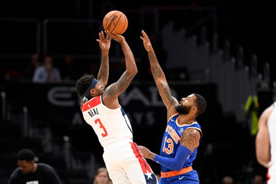 Washington Wizards guard Bradley Beal (3) shoots against New York Knicks forward Marcus Morris (13) during the first half of an NBA preseason basketball game, Monday, Oct. 7, 2019, in Washington. (AP Photo/Nick Wass)