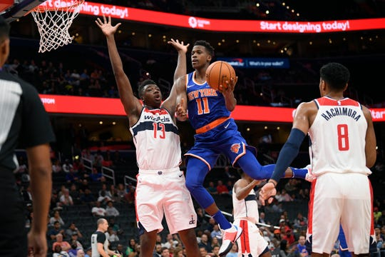 New York Knicks guard Frank Ntilikina (11) goes to the basket against Washington Wizards center Thomas Bryant (13) and forward Rui Hachimura (8) during the first half of an NBA preseason basketball game Monday, Oct. 7, 2019, in Washington. (AP Photo/Nick Wass)