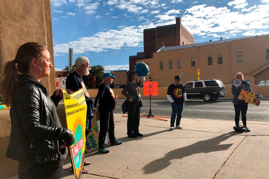 Protesters gather outside an annual meeting of the New Mexico Oil and Gas Association to urge more aggressive action against climate pollution in Santa Fe Tuesday, Oct. 8, 2019. Inside, New Mexico Gov. Michelle Lujan Grisham praised the oil industry's role in underwriting public education and solicited its help in developing new state regulations for methane emissions, and U.S. Interior Secretary David Bernhardt described federal deregulation efforts.