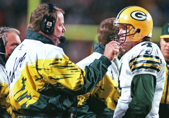 Green Bay Packers quarterback Brett Favre talks with head coach Mike Holmgren on the sideline.