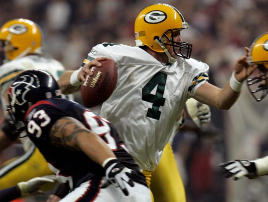 Green Bay Packers quarterback Brett Favre evades the Houston Texans pass rush before throwing a 15-yard completion during the second quarter of a Nov. 21, 2004, game at Reliant Stadium in Houston.