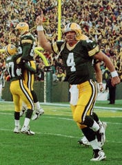 Green Bay Packers quarterback Brett Favre (4) reacts after throwing an 80-yard touchdown pass to receiver Antonio Freeman in the first quarter Sunday, Nov. 1, 1998, against the San Francisco 49ers in Green Bay, Wis. Also celebrating are Robert Brooks (87) and Antonio Freeman. The Packers won 36-22.