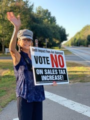 Martha Anderson smiles and waves at passerby on Woodbine Road as she holds a sign opposing the penny tax increase on Tuesday, Oct. 8, 2019.