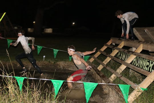 "Three brave souls approach the final stretch of mud before the finish line at the Black Swamp Runner's 7th annual ""Night of the Dead"" run on Saturday."