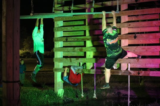 "A group of racers make their way across one of the most difficult obstacles at the 7th annual ""Night of the Dead"" mud run on Saturday."