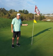 Jon Strathmeyer holds his golf ball after making a hole-in-one on the 290-yard fourth hole at Bridgewater Golf Club.