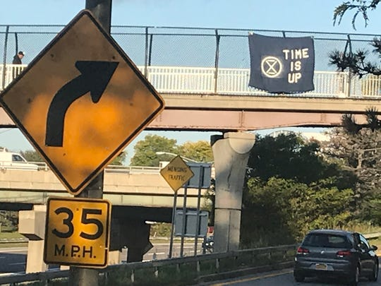 A climate-change protest sign hangs above Interstate 490 on Tuesday, Oct. 8, 2019.
