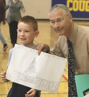 Grant School third-grader Stephen Steiner poses for a photo with Principal-Superintendent Robert Effa. Stephen drew a poster of the White House where Effa will visit after winning an award for being California's No. 1 elementary school principal while he was at at Grand Oaks Elementary School in Shasta Lake.