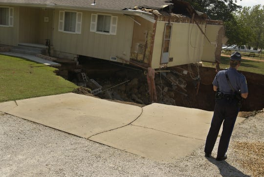 A home in Nixa teeters above the 75-foot-deep sinkhole that collapsed in 2006.