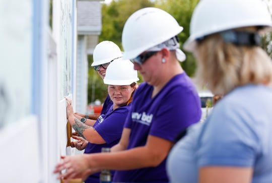 "Bridget Cover uses a guide to make sure siding is spaced correctly as she works on a house as part of Habitat for Humanity's Women Build program on Saturday, Oct. 5, 2019. Cover is working on her ""sweat equity"" hours for Habitat for Humanity's home-buying program."