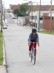 Ginger Stringer pedals north along Campbell Avenue in downtown Springfield. On Tuesday, City Council heard a presentation on the possibility of making stretches of road on Campbell and Jefferson two-way.