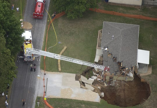 Firefighters observe the sinkhole that collapsed beneath a Nixa home in 2006.