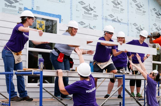 Volunteers hang siding as they work on a house as part of Habitat for Humanity's Women Build program on Saturday, Oct. 5, 2019.