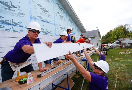 M'Liss Hay hands a piece of siding up to other volunteers as they work on a house as part of Habitat for Humanity's Women Build program on Saturday, Oct. 5, 2019.