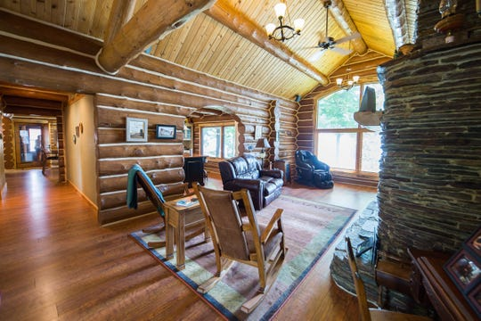 The living room features an exposed logvaulted ceiling and a spectacular full-length fireplace and hearth.