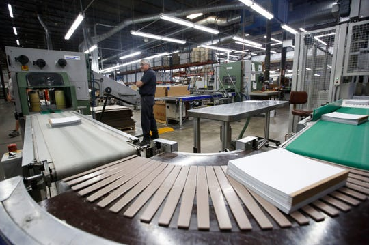 Stacks of notebooks are advanced along the production line on Thursday, Oct. 3, 2019, at Worzalla in Stevens Point, Wis. The printing company announced a major expansion of its production facilities on Monday.