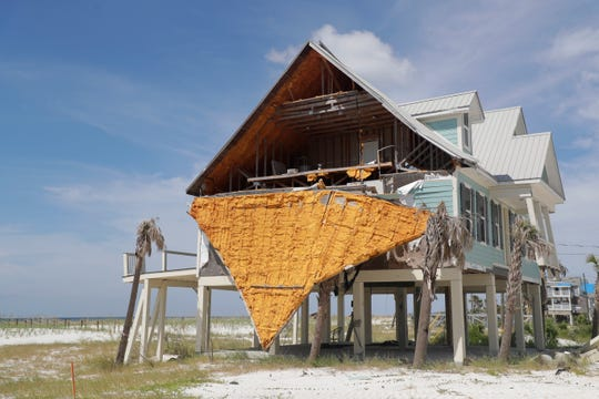 The ripped away wall of a beachside home still hangs off one year after Hurricane Michael.
