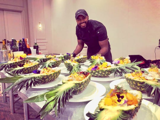 Sam Burgess, 26-year-old entrepreneur and chef behind the Pineappétit food truck, prepares pineapple bowls.