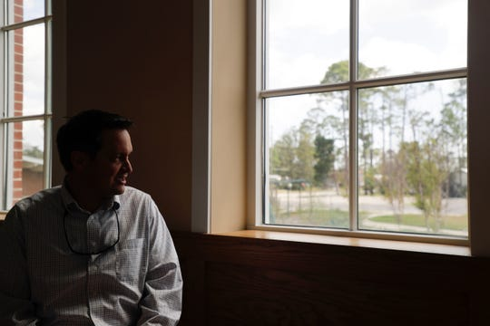 First United Methodist Church of Port St. Joe Pastor Geoffrey Lentz looks out the window of the church to where his house once stood before it was ripped down by Hurricane Michael last year.