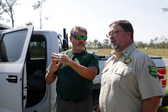 Florida Forest Service Mitigation Specialist Steve Weherley and Forest Area Supervisor Steve Oswald discuss a field of slash pine trees along Highway 274 that were destroyed by Hurricane Michael last year.
