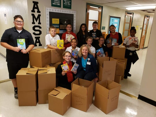 Beth Daddario (center), director of volunteers, retail and guest services at Inspira Health, is joined by students from Vineland's Applied Math and Science Academy who donated the most books in their homeroom as part of a kindness project.