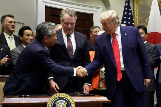 President Donald Trump shakes hands with Japanese Ambassador to the United States Shinsuke Sugiyama, left, and U.S. Trade Representative Robert Lighthizer after they signed a trade agreement in the Roosevelt Room of the White House, Monday, Oct. 7, 2019, in Washington.