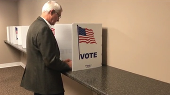 Board of Elections Director Tim Thompson demonstrates early in-person voting procedures at the board office in downtown Zanesville.