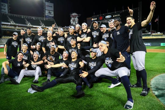 Yankees players celebrate on the field after sweeping the Twins in the ALDS.