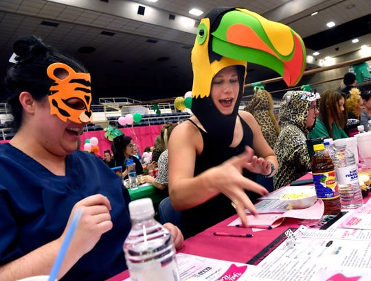 Tiffany Walker-Fox, (left) watches as Jenn Moran plays a round during Bunco for Breast Cancer at the Taylor County Coliseum. This year the charity event went with a jungle theme this year.