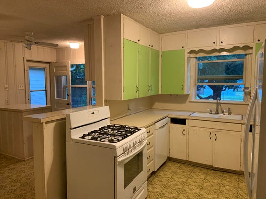The Jaklewicz kitchen, with cabinets and the stove halving the room and green cabinet doors. And the beloved linoleum.  2019