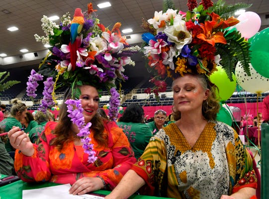 Katherine Rinard (left) looks at Leigh Anne Holden as she throws the dice while balancing the floral display on her head to prevent it from tipping over during Tuesday's Bunco for Breast Cancer at the Taylor County Coliseum,