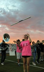 Megan Colwell, a senior, prepares to catch her rifle during Wylie High School's Pure Gold Band rehearsal at daybreak Wednesday at Bulldog Stadium.
