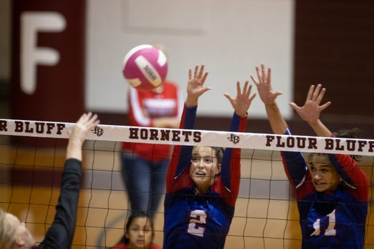 Gregory-Portland's Samantha Kuzma and Chloe Rodriguez jump to block a spike during their game against Flour Bluff's at Flour Bluff High School on Tuesday, Oct. 8, 2019.