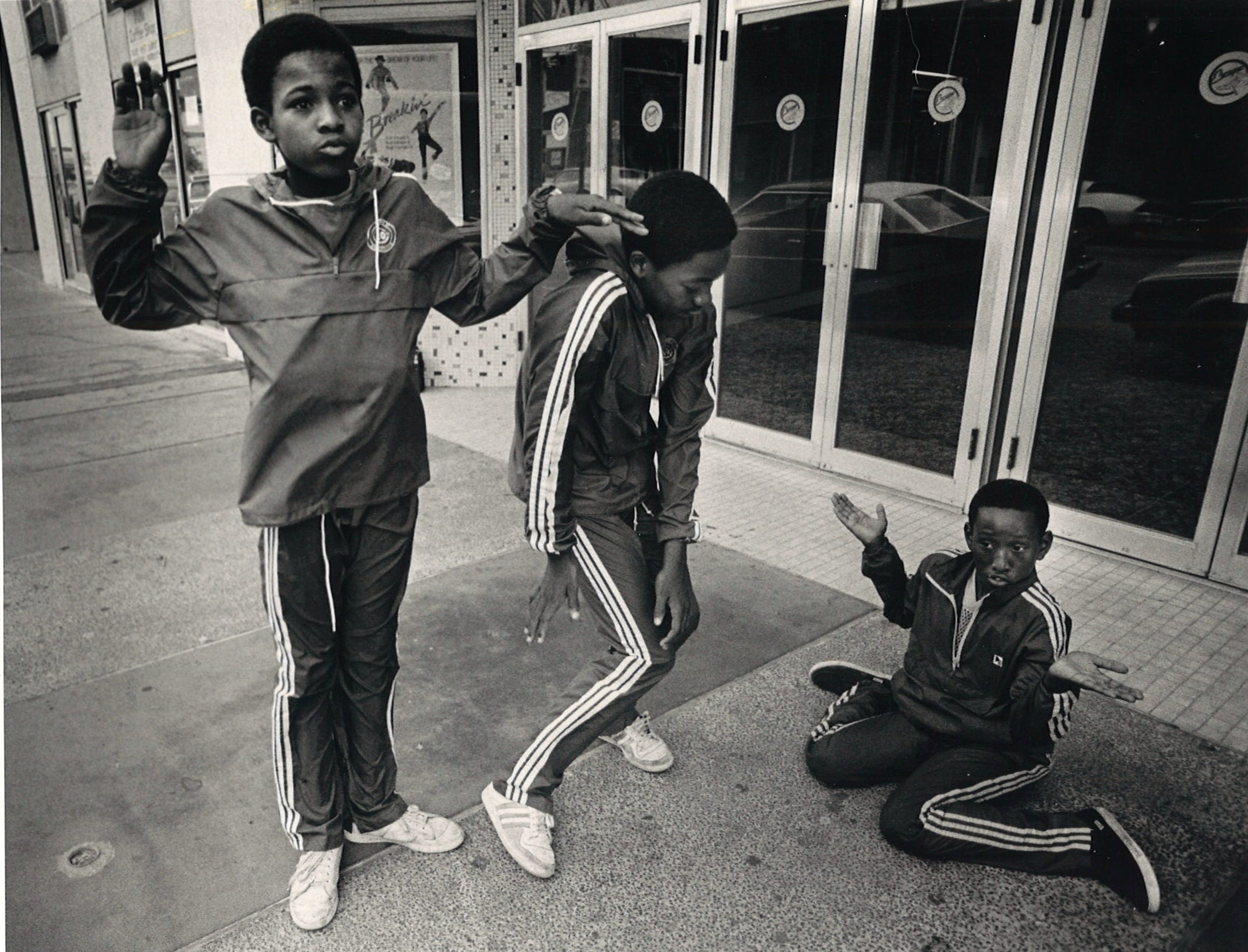 "Cosmic Crew dancers Derrick Mosely (left to right), 12, Tyrone Clay, 14, and Jermaine McDowell, 11, pop and lock in front of Centre Theatre on Chaparral Street in downtown Corpus Christi on July 5, 1984. The breakdancing crew were heading inside to watch ""Breakin."""
