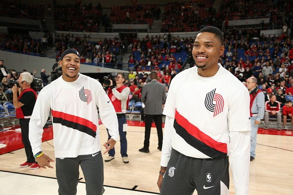 Troy Caupain (left) of the Portland Trail Blazers and Kent Bazemore smile prior to a preseason game against the Denver Nuggets on October 8, 2019 at the Veterans Memorial Coliseum in Portland, Oregon.