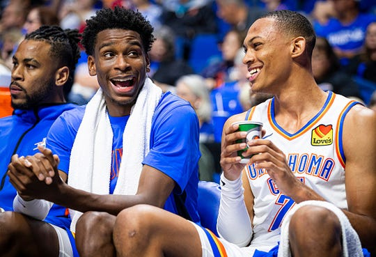 Shai Gilgeous-Alexander (left) and Darius Bazley of the Oklahoma City Thunder share a conversation during a game against the Dallas Mavericks on October 8, 2019 at BOK Center in Tulsa, Oklahoma.
