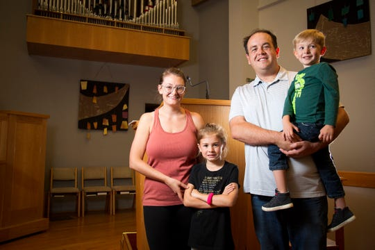 Pastor Alex Hoops poses with his wife Emily Hoops, daughter Amelia and son Harvey in the sanctuary at Good Shepherd Lutheran Church in Kenwood, Ohio, on Tuesday, Oct. 8, 2019.