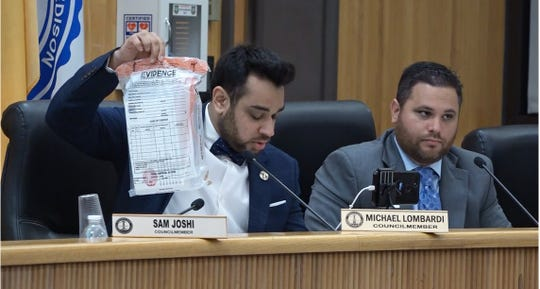 Edison Councilman Sam Joshi holding a back containing evidence from the U.S. Postal Inspection Service related to the 2017 racist campaign flyers.
