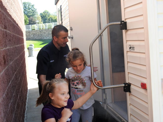 Fire Prevention Officer Brent Endsley of the Coshocton Fire Department helps third-graders Lily Dile and Emma Gambill to exit the department's fire safety trailer during a demonstration involving smoke this week at Coshocton Elementary School for National Fire Prevention Week.